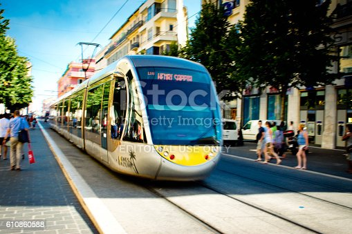 Nice, France - July 29, 2015: Tram on rails travelling through tourists in central Nice, France. This is near the cathedral Notre Dame.
