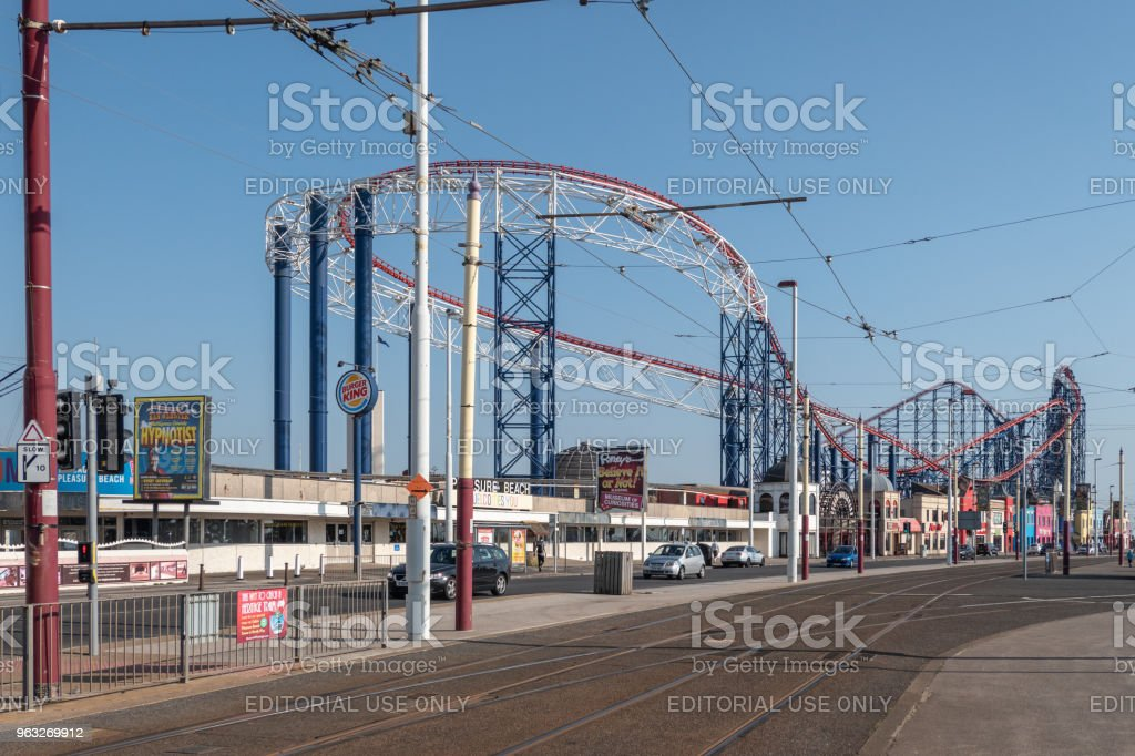 Tram lines along the seafront in Blackpool, with rollercoaster track stock photo