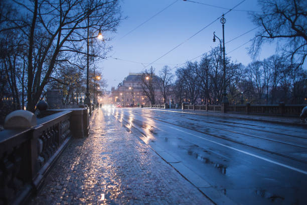 tram lines and puddles in the evening in rain stock photo