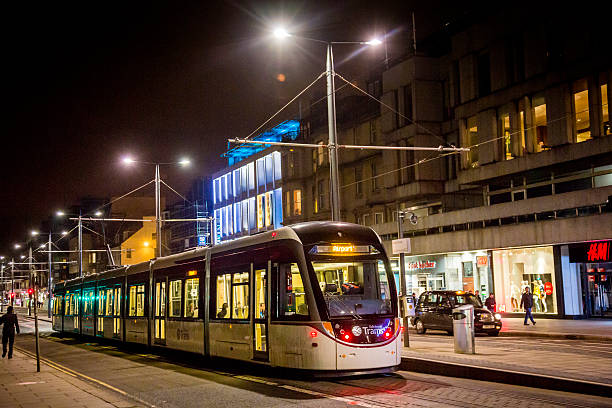 Tram on Princes Street, Edinburgh, at night Edinburgh, UK - March 15, 2015: A tram on Princes Street in the heart of Edinburgh at night. People are on the tram and pedestrians are walking along the street in front of lit shops in the background. princes street edinburgh stock pictures, royalty-free photos & images