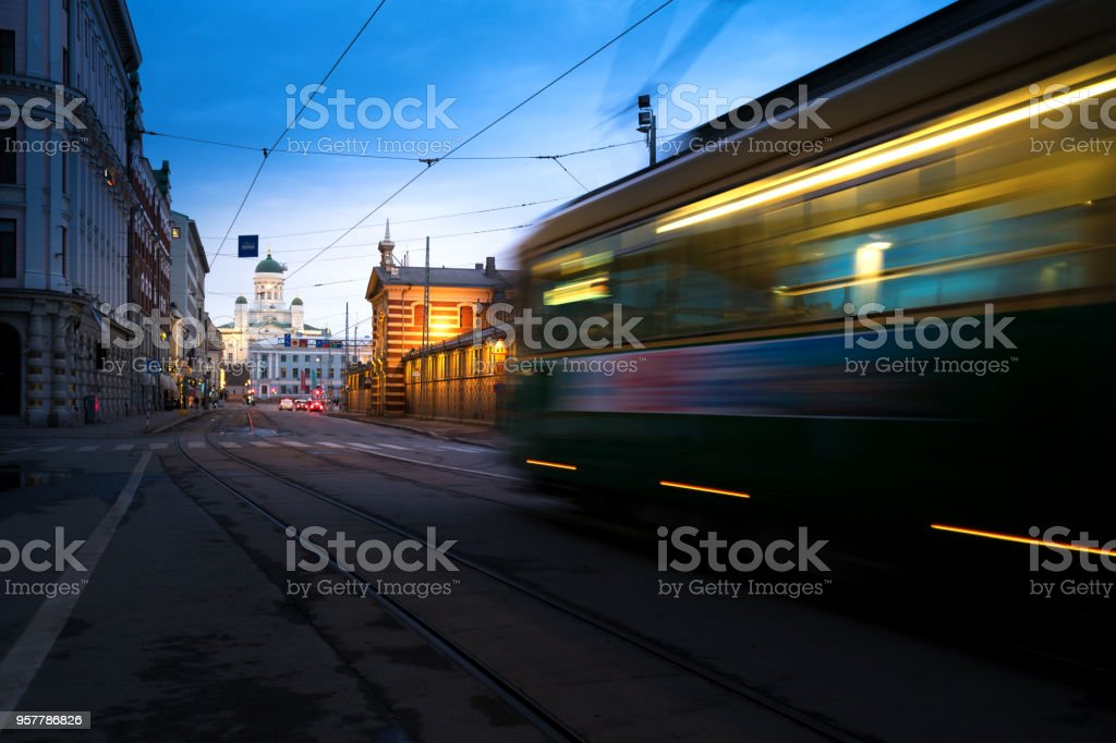 Tram passing Helsinki Senate Square during sunset with Helsinki Cathedral in the background at Finland. stock photo