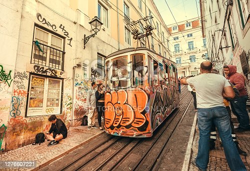 Lisbon, Portugal: People having fun near the grungy tram station, on colorful street with historical houses on 18 May, 2019. Portuguese language has 250 million total speakers around the world