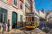 Lisbon, Portugal - February 18, 2018: two people waiting for a popular street car on a street in Lisbon