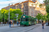 Sofia, Bulgaria - 29 April 2019: Appearance from Sofia Traffic. Tramcar, Tram, Trolleybus, Tramway at Sofia Traffic in the evening with the people and historical buildings. One senior woman and one man are coming to camera side and one young woman walking near the tram.
