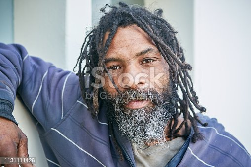 A homeless man with dreadlocks leans on a wall and looks at camera with a thoughtful but resigned expression,