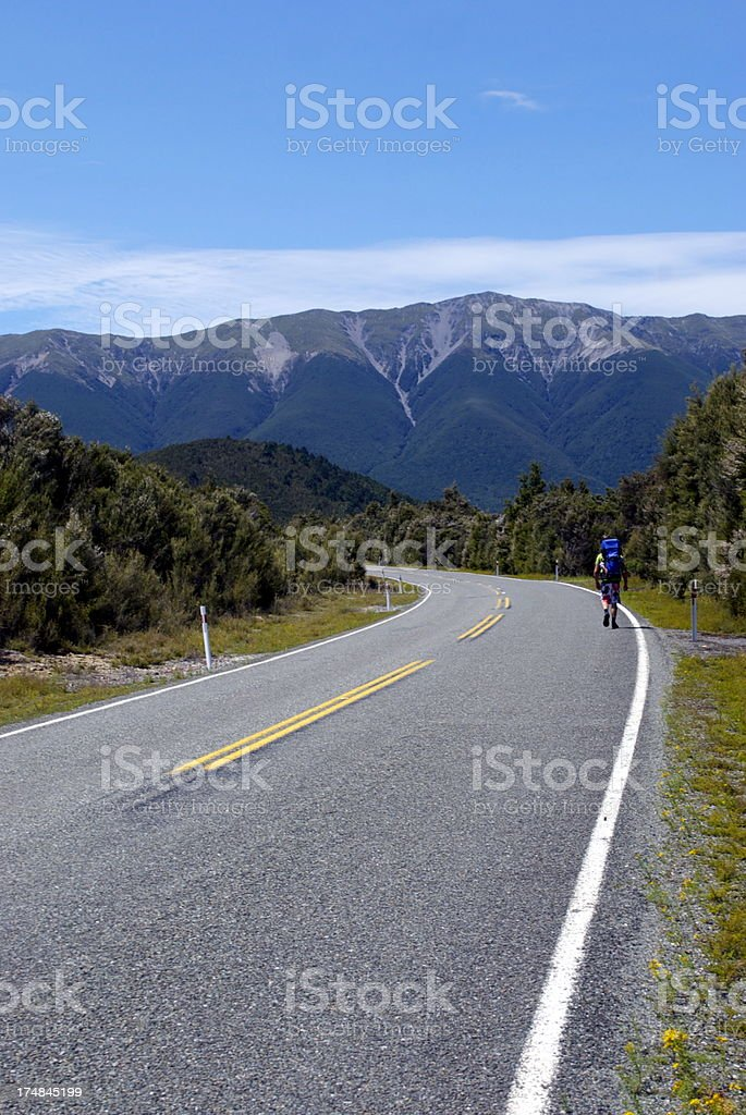 Tramper walks on road in Nelson Lakes National Park, NZ royalty-free stock photo