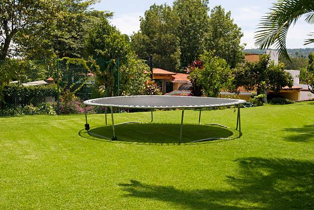 trampolin im garten - gartentrampolin stock-fotos und bilder