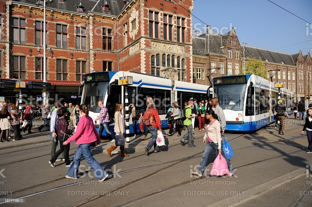 Trams and travellers in front of Amsterdam Central railway station royalty-free stock photo