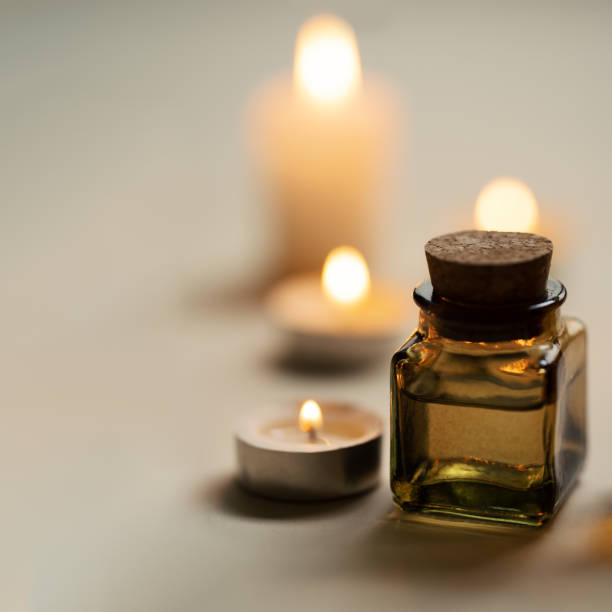 Tranquil and concise spa composition with oil flask and candles. Copy space stock photo