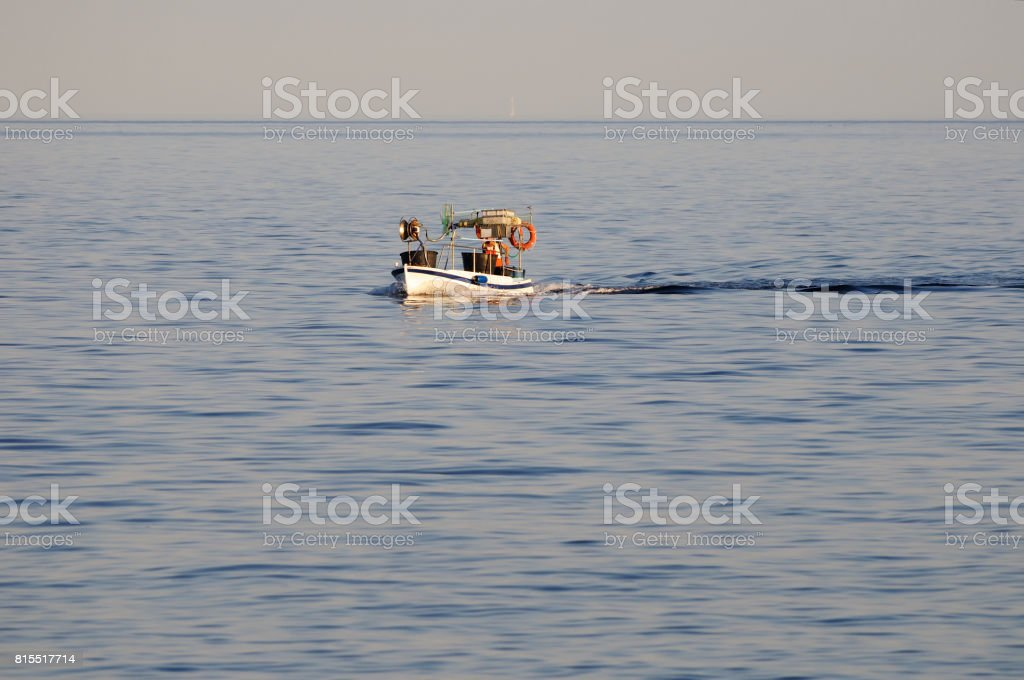 Tranquil blue waves and a fishboat stock photo