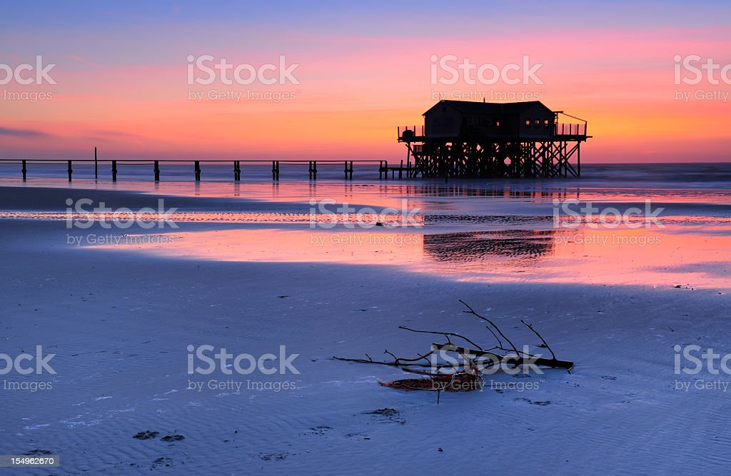 Tranquil Coastal Sunset, Jetty and Stilt House on Sand Beach stock photo