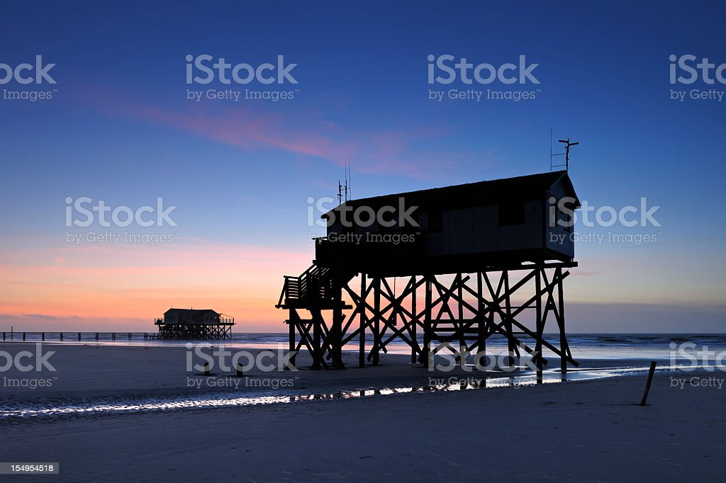 Tranquil Coastal Sunset, Jetty and Stilt Houses on Sand Beach stock photo
