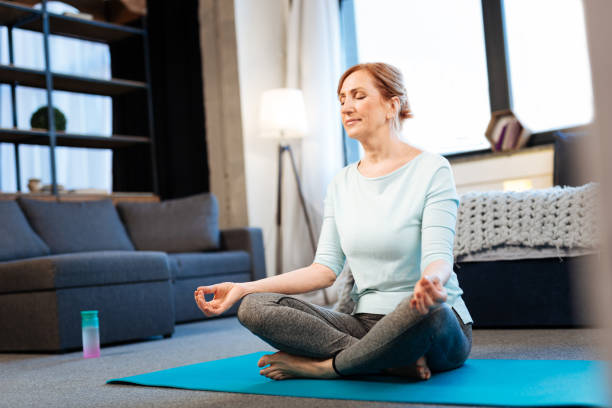 Tranquil good-looking woman meditating with closed eyes Morning meditation. Tranquil good-looking woman meditating with closed eyes while having connected fingertips meditating stock pictures, royalty-free photos & images
