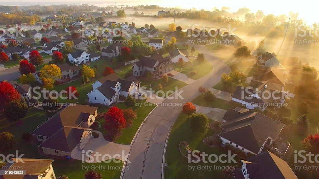 Tranquil idyllic Autumn neighborhood shrouded in fog at dawn. stock photo