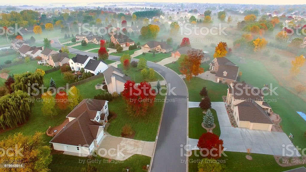 Tranquil idyllic Fall neighborhood shrouded in fog at dawn. stock photo