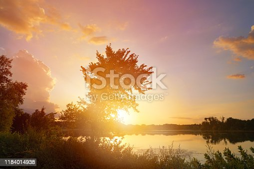 876420064 istock photo Tranquil lake at sunset with sunbeams 1184014938