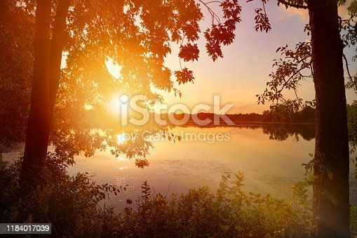 876420064 istock photo Tranquil lake at sunset with sunbeams 1184017039