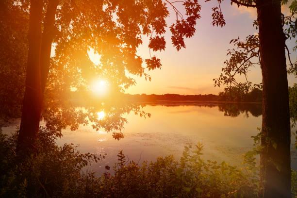 Ruhiger See bei Sonnenuntergang mit Sonnenstrahlen – Foto