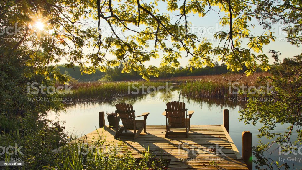 Tranquil Lake Scene With Two Adirondack Chairs Stock Photo