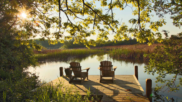 Tranquil Lake Scene with Two Adirondack Chairs Relaxing setting with two adirondack chairs on a pier over looking a calm and tranquil lake at sunrise with reflections on a Spring day wisconsin stock pictures, royalty-free photos & images