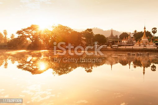 A tranquil landscape of lake and ancient buddhist temple at sunrise, glowing golden sun shines on the lake and ancient temple, famous place in Mae Hong Son, North Thailand.