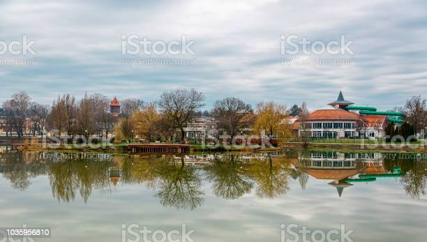 Photo of Tranquil landscape with lake, houses, cloudy sky, and trees reflected symmetrically in the water. Salt lake (Sosto) Nyiregyhaza, Hungary