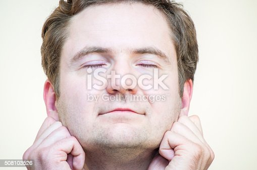 Portrait of young, elegant, Caucasian Ethnicity, tranquil, meditating man holding his earlobes on white background.