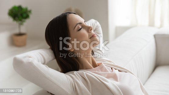istock Tranquil millennial female napping on couch with hands behind head 1310961723