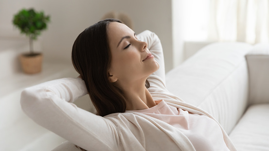 Weekend, at least!.. Tranquil peaceful millennial female enjoying freedom napping dreaming relaxing on couch with closed eyes and hands behind head meditating breathing fresh air feeling happy serene
