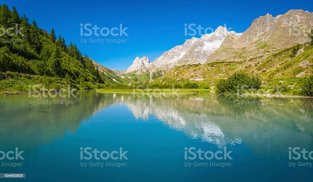 Tranquil mountain lake reflecting picturesque Alpine peaks panorama Alps Italy stock photo