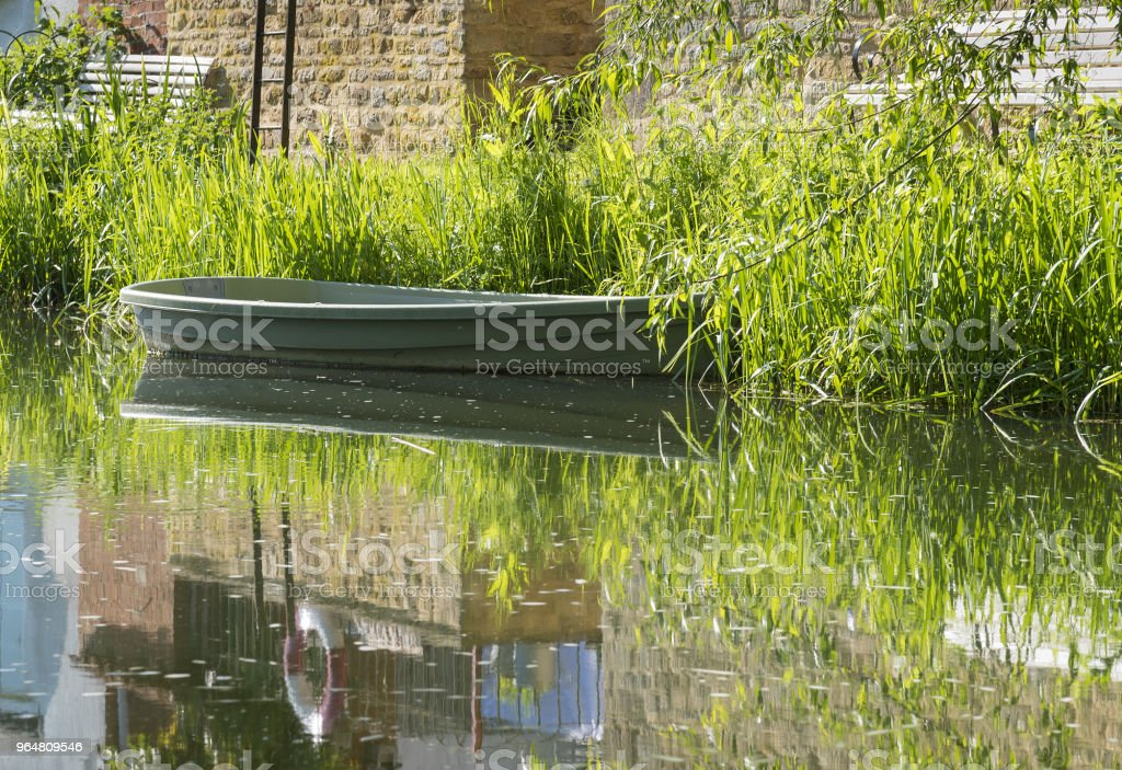 Tranquil river scene with empty rowing boat moored at the bank. royalty-free stock photo