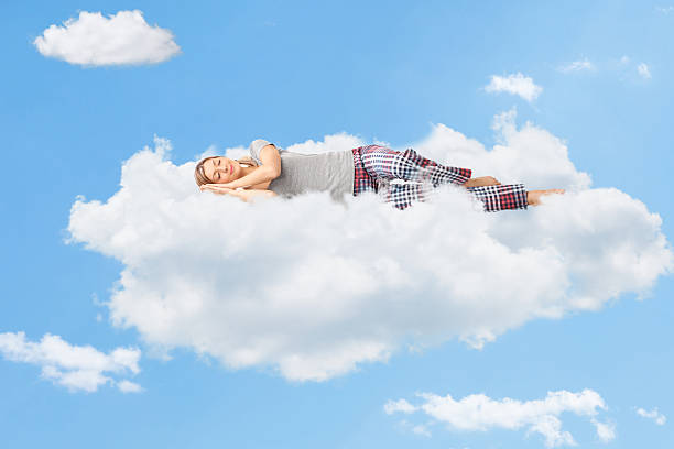Tranquil scene of a woman sleeping on cloud Tranquil scene of a young woman dreaming and sleeping on a cloud up in the sky tranquil scene stock pictures, royalty-free photos & images