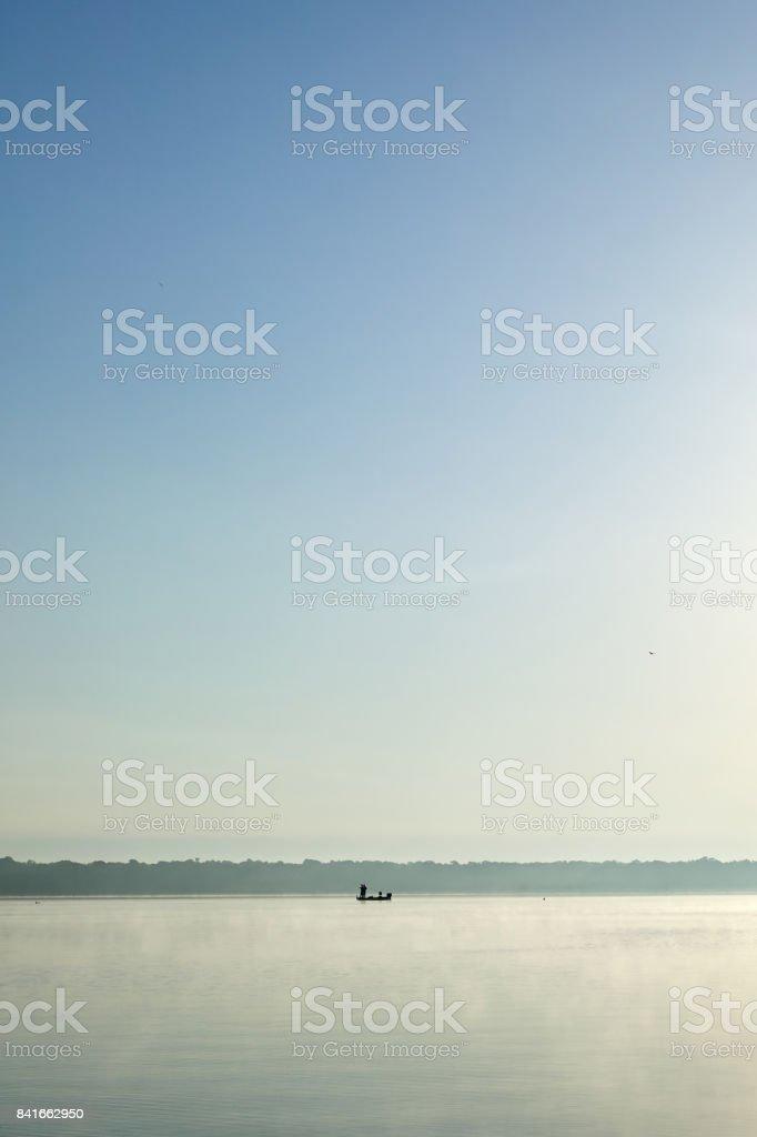 Tranquil scene of fishing boat in calm lake stock photo