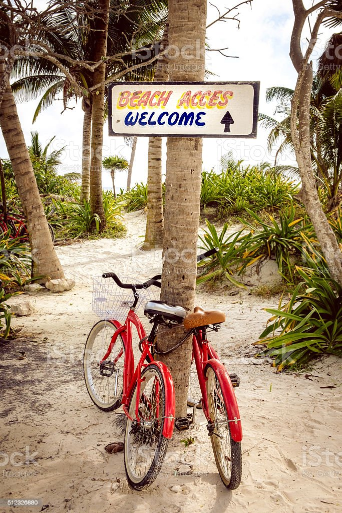 Tranquil scene with two bicycles, beach and palms Tranquil scene with two bicycles, beach, palms and welcome sign Accessibility Stock Photo
