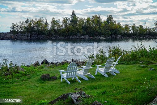 876420064istockphoto Tranquil scene with white wooden lawn chairs on green grass overlooking Lake Superior in Northern Minnesota 1058007954