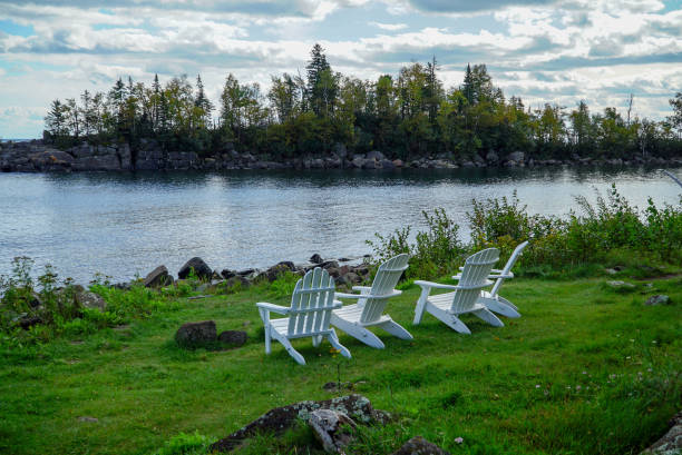 Tranquil scene with white wooden lawn chairs on green grass overlooking Lake Superior in Northern Minnesota stock photo
