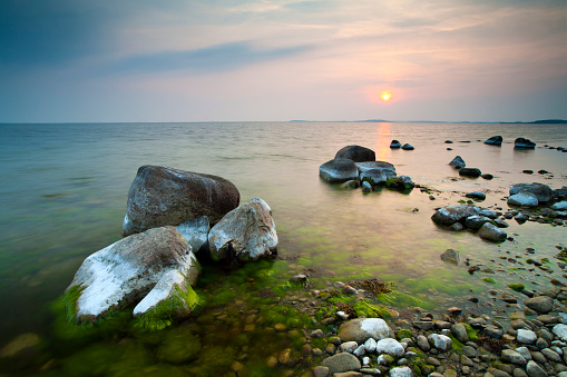 Tranquil Seascape with Huge Boulders on Rocky Coastline at Sunset