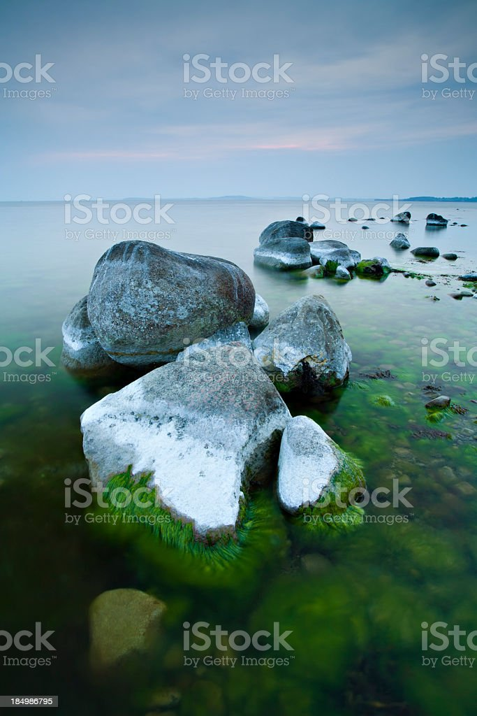 Tranquil Seascape with Huge Boulders on Rocky Coastline at Sunset royalty-free stock photo