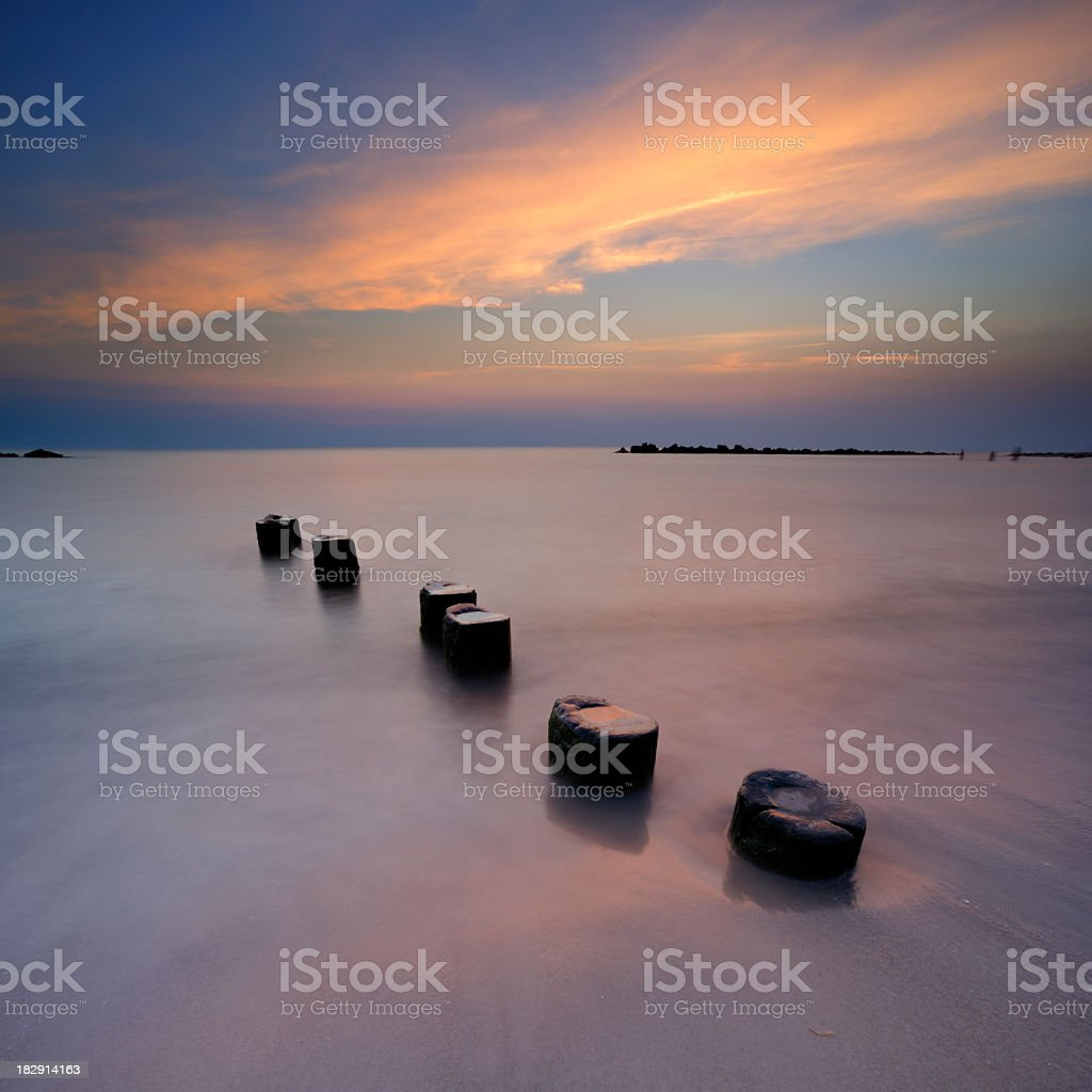 Tranquil Seascape with Old Wooden Posts at Sunset royalty-free stock photo