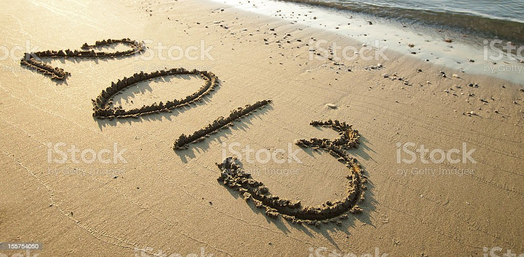 Tranquil seashore with 2013 drawn on sand royalty-free stock photo