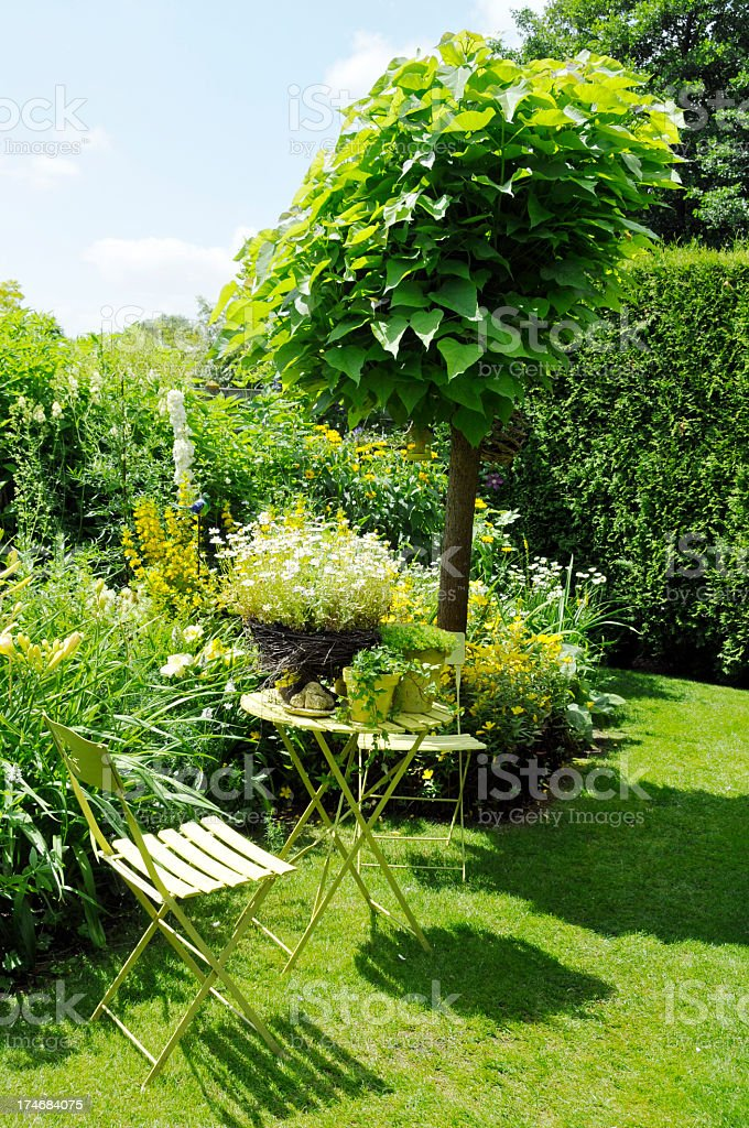 Tranquil sitting corner with catalpa tree,folding chairs,side table stock photo