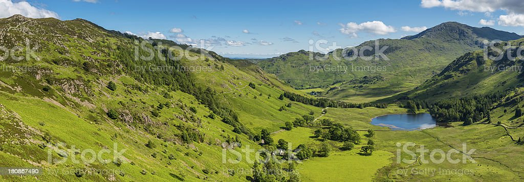 Tranquil summer valley panorama idyllic mountain peaks in green landscape stock photo