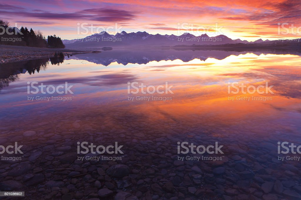 tranquil sunset at lake forggensee in bavaria - germany stock photo
