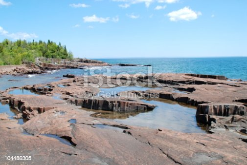 The rugged beauty of the North Shore in Minnesota is a sight to behold. It takes my breath away every time. This scene shows the pools of water that form atop the huge basalt slabs when the storms come in. The waves lap up and over the rock, catching in all the crevices and creating their own mini-lakes that reflect the bright, blue sky.