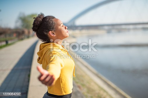 Spiritual mid adult African American woman with arms open meditating on sunrise.
