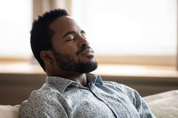 Tranquil young african man resting eyes closed breathing on couch Tranquil calm young african american man resting with eyes closed taking deep breath of fresh air enjoy comfort relaxing on couch feel peace mind and stress relief meditate at quiet home sit on sofa relief emotion stock pictures, royalty-free photos & images
