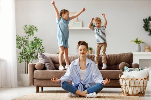 Ruhige junge Mutter übt Yoga, um ruhig mit schelmischen Kindern zu Hause zu bleiben – Foto