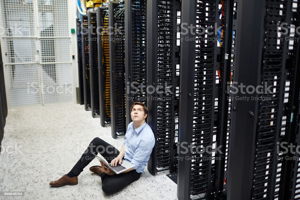 Young man with laptop sitting on the floor and leaning by bitcoin...