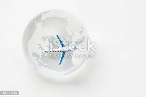 An image of a transatlantic travel by plane. A miniature jet plane is flying over the crystal globe.