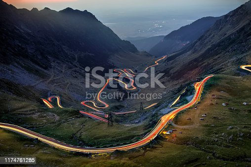 The Transfagarasan curved road seen with car trail lights at the blue hour. Photo taken on 31st of August 2019, Sibiu county, Romania.